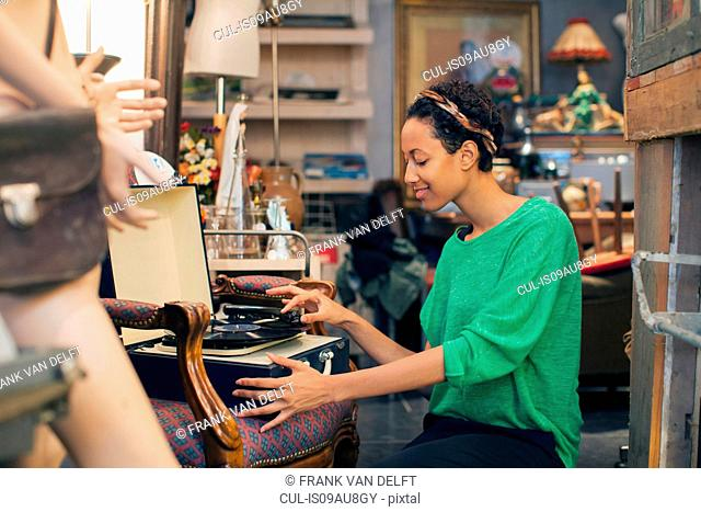 Young woman playing vinyl records in vintage shop