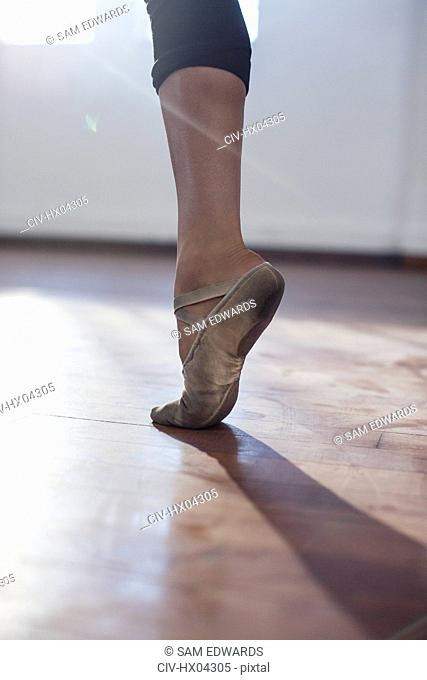 Close up young female ballet dancer practicing in ballet shoe