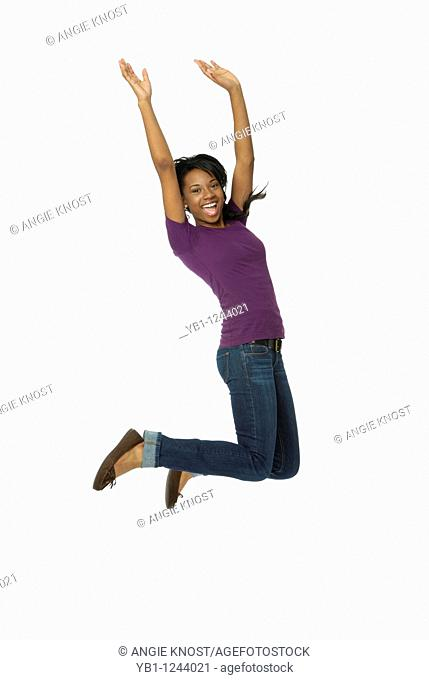 Happy teenage girl jumping in the air, on white background