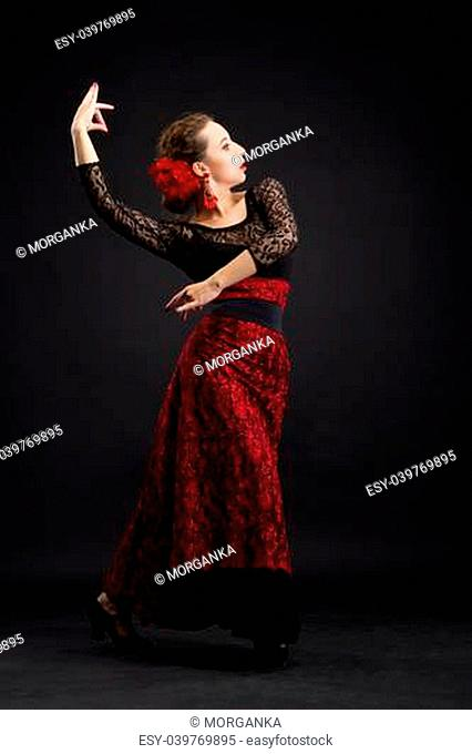 Flamenco dancer in white dress with red earrings over dark background