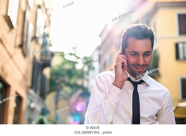 Mid adult businessman strolling down city street making smartphone call, Milan, Italy