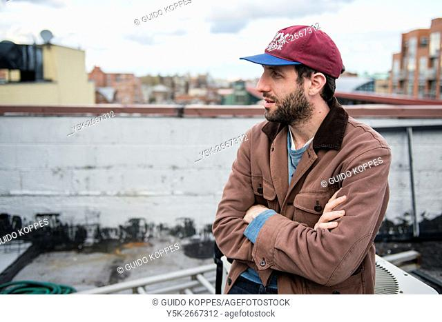 New York City, USA. Young urban male giving a tour through the Roosevelt Avenue neighborhood in Queens