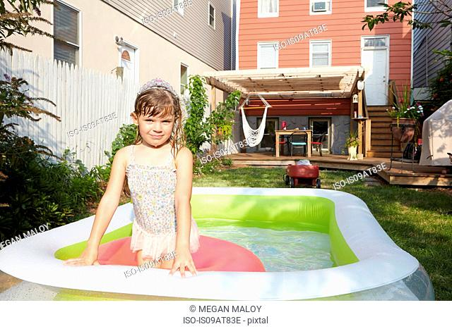 Girl sitting on inflatable floating in pool