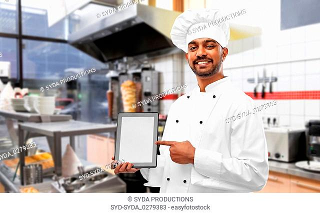 happy indian chef with tablet pc over kebab shop