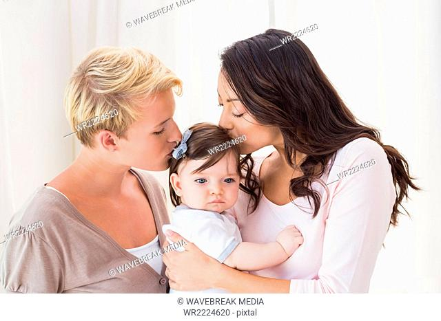 Lesbian couple kissing their baby girl