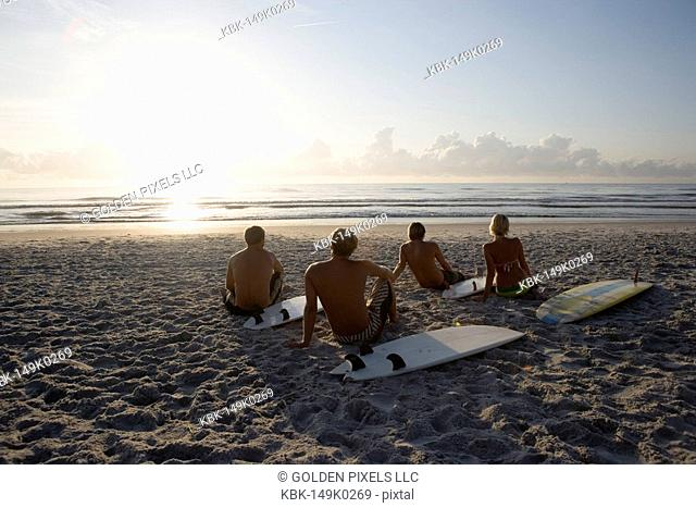 Surfer dudes and girl sitting on beach at sunrise with surfboards