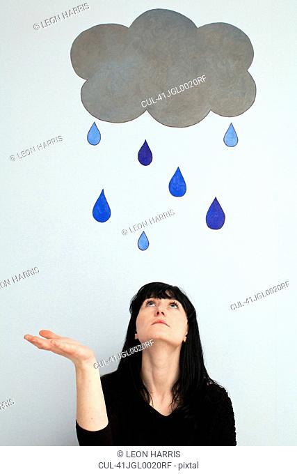 Woman standing under painted rain cloud
