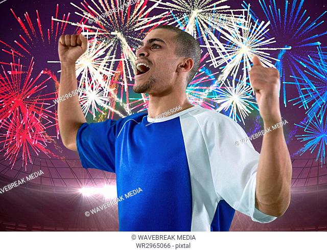soccer player wining, firework behind him