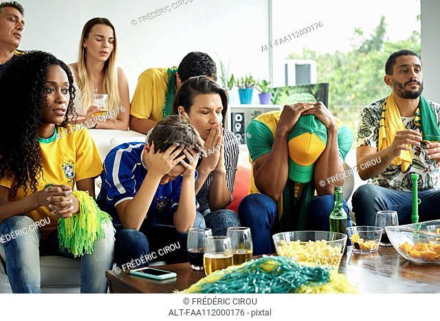 Brazilian football fans watching football match at home