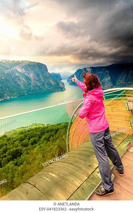 Tourist woman on Stegastein viewpoint enjoying Aurland fjord view making thumb up gesture sign, Sogn Og Fjordane, Norway