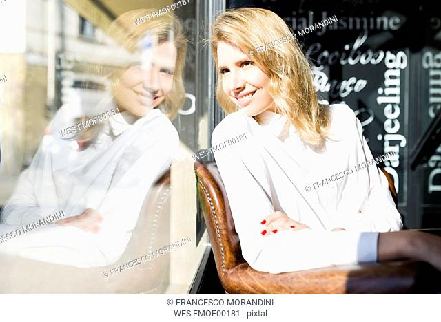 Smiling businesswoman in a cafe looking out of window