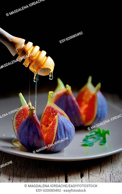 Figs with honey on wooden background