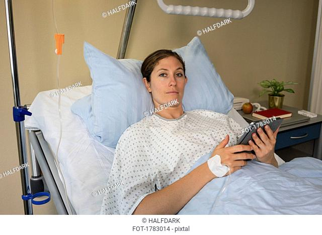 Portrait serious female patient with digital tablet, resting and recovering in hospital room