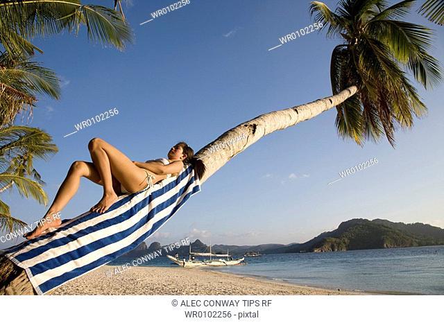 Philippines, El Nido bay. Philippino woman lying on palm tree trunk