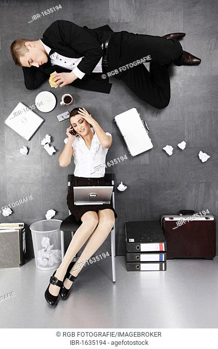 Sitting businesswoman and businessman on the floor, irritating pers