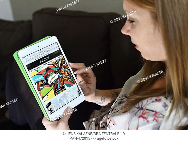 ILLUSTRATION - A young woman browses on her tablet computer through the web page of online retailer Juniqe in Berlin, Germany, 19 March 2014