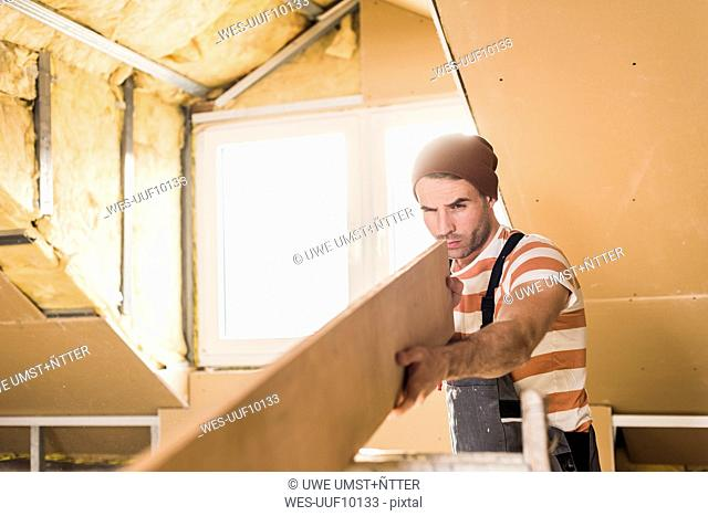 Young man checking plank on construction site