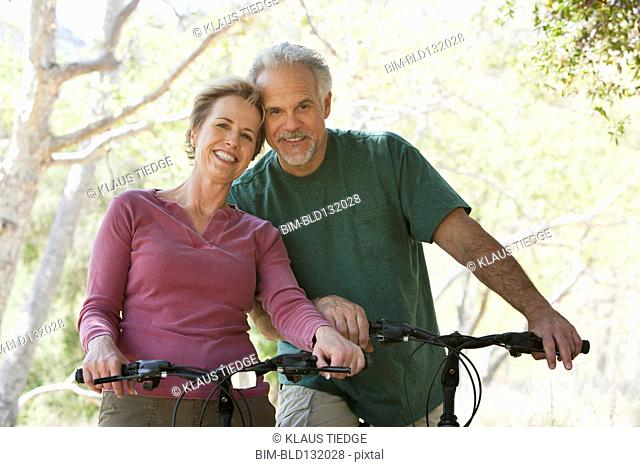 Senior Caucasian couple riding bicycles on rural path