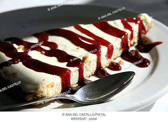 Closeup of cheese cake with jam on a plate