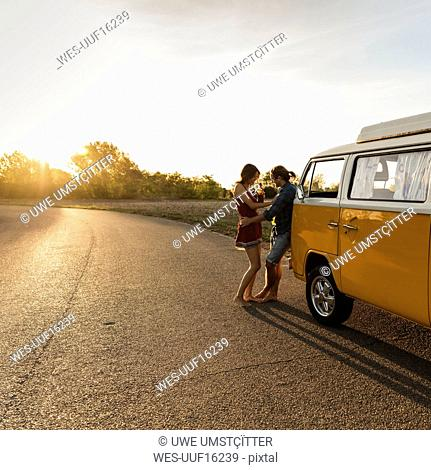 Happy couple taking a break on their road trip, having a drink at sunset