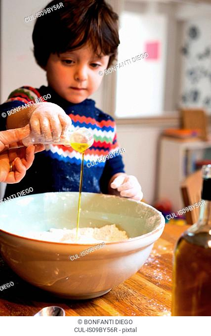 Toddler helping mother pour oil into flour in mixing bowl