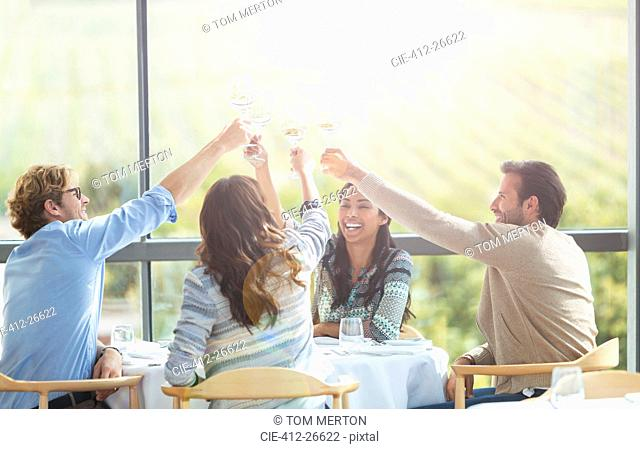 Friends toasting wine glasses overhead at winery dining room table