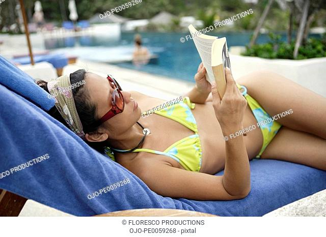 Woman lying by pool with book