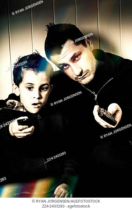 Light leaks picture of a dad and his little boy fighting for control over the television station with remote controls