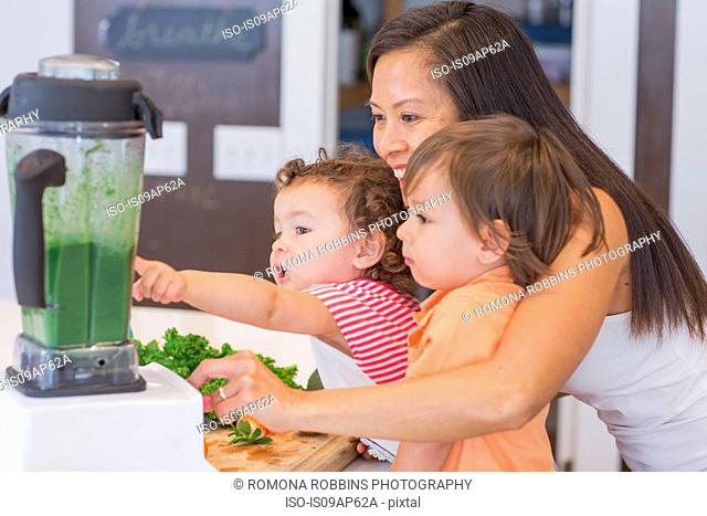 Mid adult woman making green smoothie for two toddlers in kitchen
