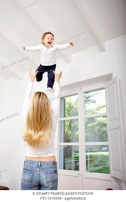 Mother throwing her one year old boy in the air
