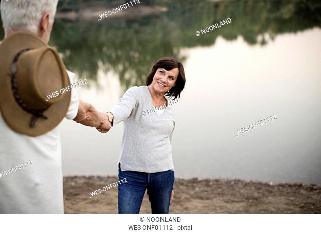 Happy senior couple hand in hand at a lake