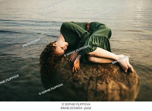 Caucasian woman wearing dress laying on rock at beach
