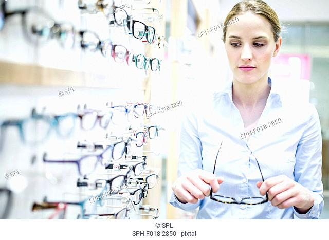 Woman holding glasses near glasses rack in optometrist's shop