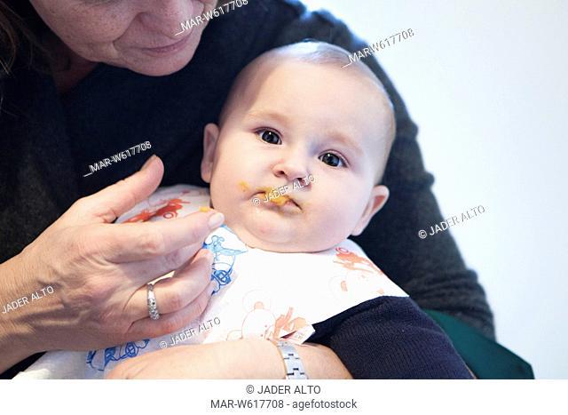 una nonna mentre da la pappa ad una neonata di 6 mesi