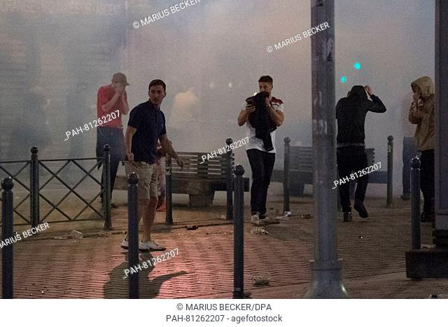 A crowd of soccer fans is seen after police used teargas in Lille, France, 15 June 2016. England will face Wales in a UEFA EURO 2016 group B preliminary round...