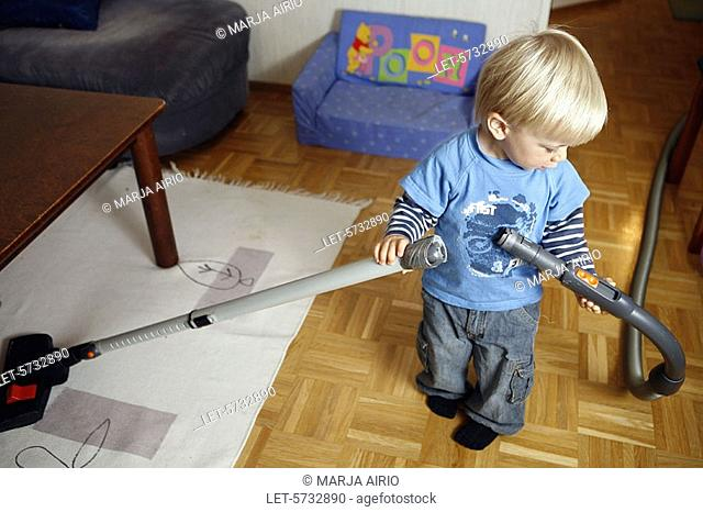 A two-year-old little boy is hoovering at home
