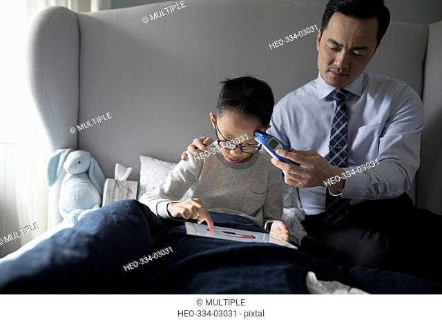 Father with thermometer checking temperature of son sick with fever
