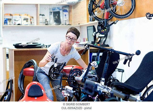 Woman in bicycle workshop checking pedal on recumbent bicycle