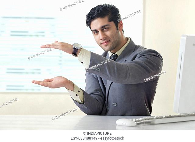 Businessman gesturing towards something