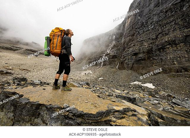 A backpacker in alpine talus on the lower flanks of Mount Assiniboine, British Columbia