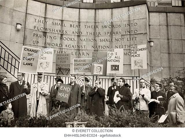Conscientious objectors from the War Resisters League picketing near the United Nations in New York City. In front of biblical quotation inscribed behind them
