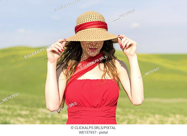 San Quirico d'Orcia, Orcia valley, Siena, Tuscany, Italy. A young woman with straw hat