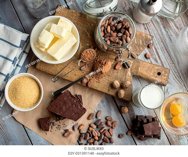 glass of milk, cane sugar, fresh butter, cocoa powder and beans, pieces of cocolate, spices and raw eggs on the wooden table
