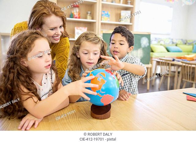 Students and teacher examining globe in classroom