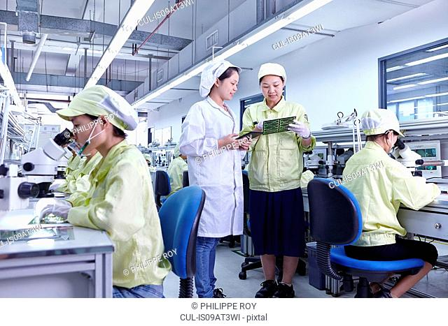 Supervisor overseeing work at quality check station at factory producing flexible electronic circuit boards. Plant is located in the south of China, in Zhuhai