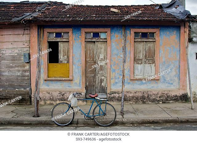 A bicycle parked in front of a funky small house