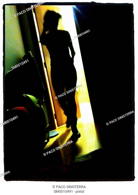 Silhouette of woman walking out the door Spain