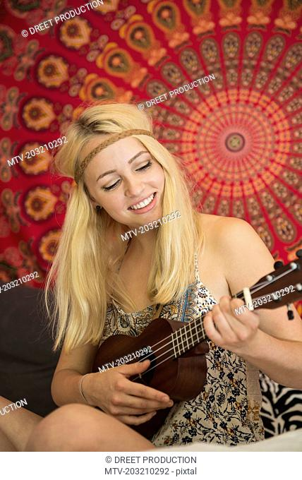 Young woman playing ukulele in the bedroom, Bavaria, Germany