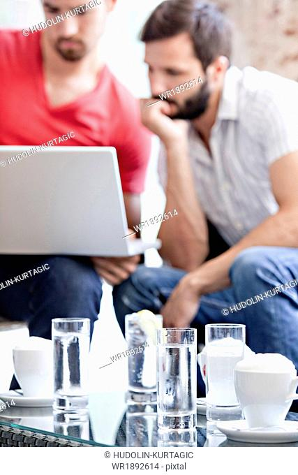Two male university students in cafe working on laptop