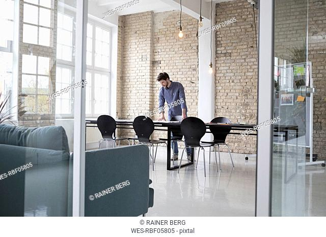 Young entrepreneur standing in his office, looking at plans